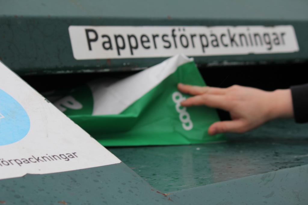 """En person slänger en papperspåse i en container märkt """"pappersförpackningar"""" på en återvinningscentral."""