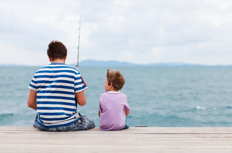 Far med barn som fiskar.